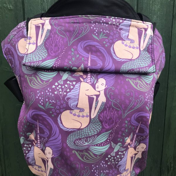 Integra sling shows a mermaid holding a hand gently under the chin of a unicorn, on a purple background integra sling