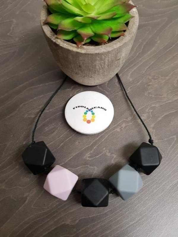 Hemp cord necklace with black and grey geometric beads, with a pale pink feature bead