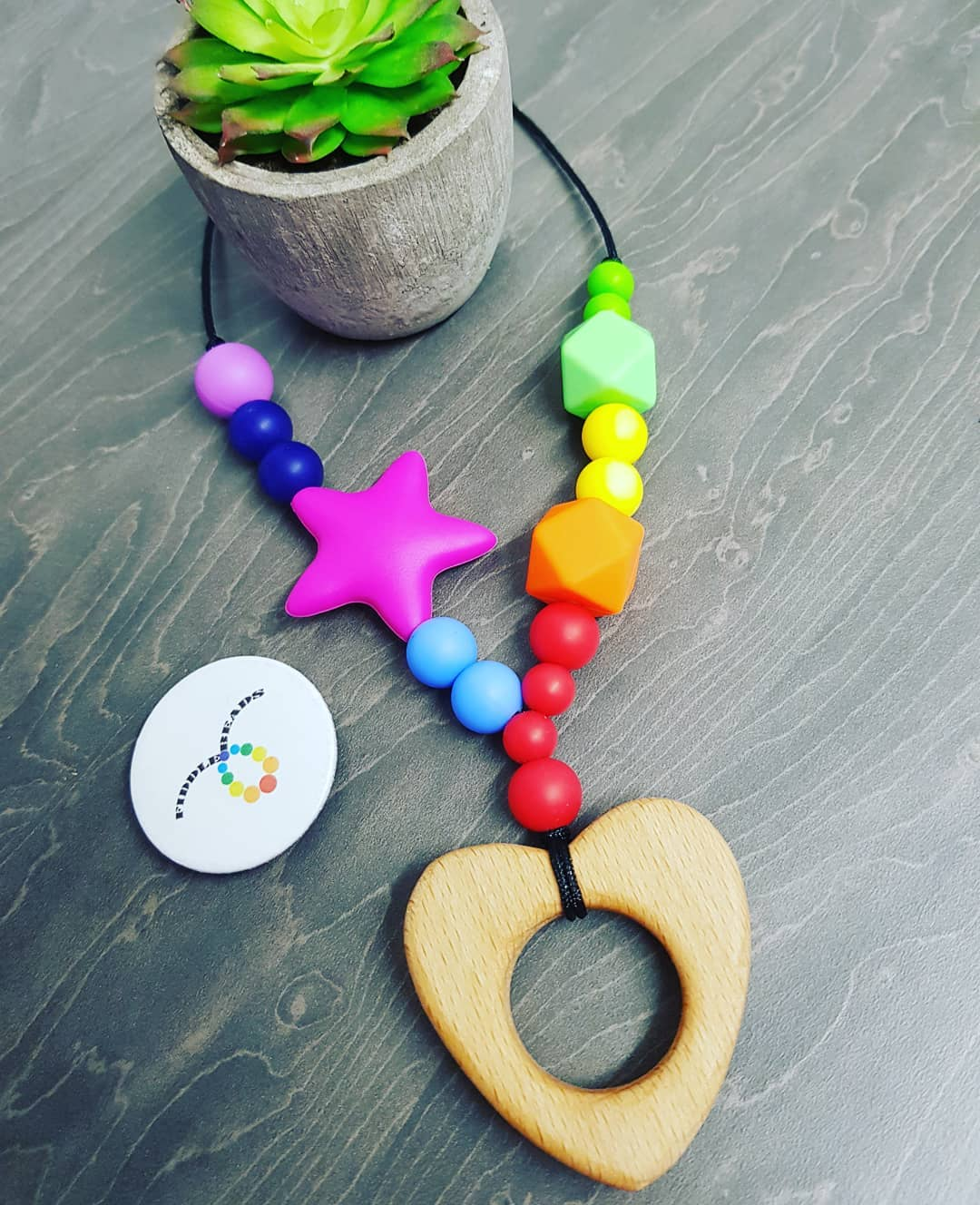 Hemp cord necklace with rainbow colours, a feature purple star, and a wooden heart teether
