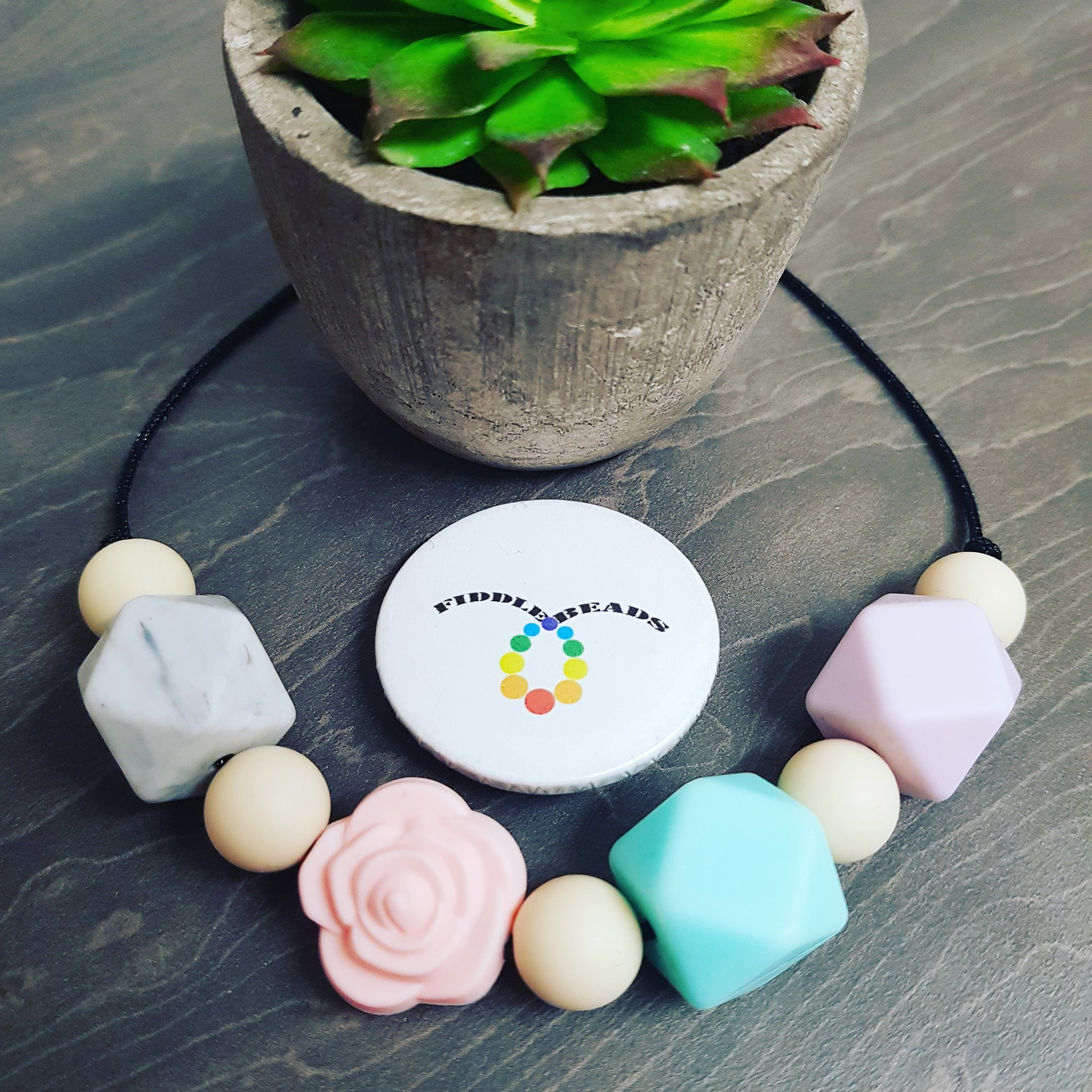 Pastel coloured fiddle necklace with silicone geometric shape beads, separated by small wooden balls, including a signature rose bead. Made using hemp cord. Commonly used when breastfeeding and babywearing, brilliant for teething babies