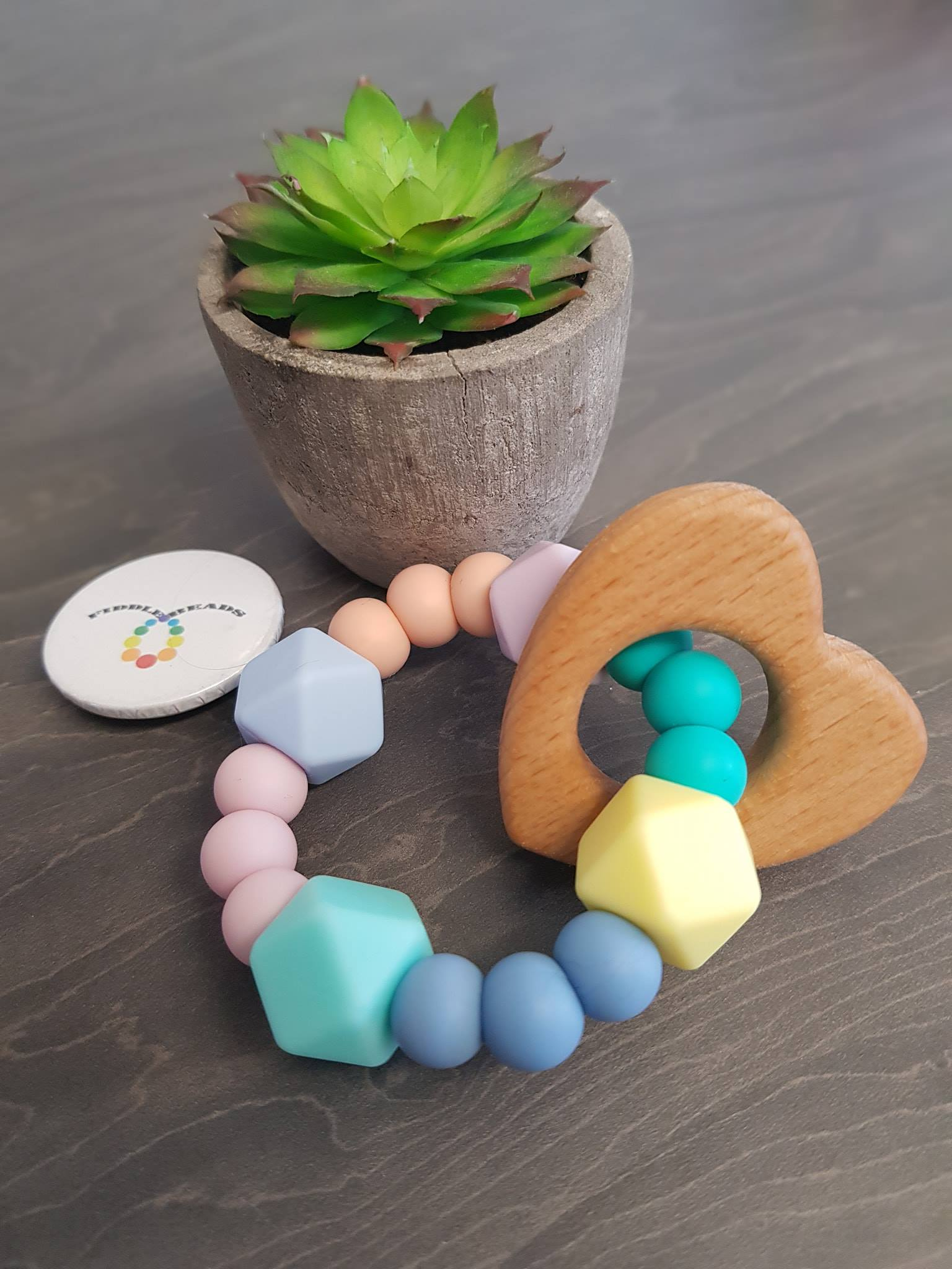 Teether toy ring made with hemp cord and pastel silicon beads and a featured wooden heart